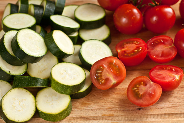 Разогрейте духовку до 200 градусов.  Молодые кабачки нарежьте ломтиками толщиной около сантиметра. Если у вас крупные помидоры, их лучше порезать ломтиками, если черри — просто пополам.