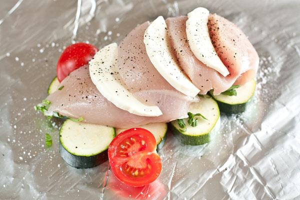 На большой лист фольги выложите несколько кружочков кабачков и помидоры. Посолите, поперчите и посыпьте мелко нарезанными листьями базилика.  В филе куриной грудки сделайте глубокие надрезы (немного наискосок) и в каждый надрез вложите ломтик моцареллы.  Подготовленную грудку положите поверх овощей, еще раз посолите, поперчите и посыпьте базиликом. Сверху немного полейте оливковым маслом.