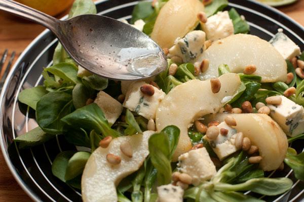 На листья салата выложите груши, нарезанный кубиками сыр, посыпьте орешками и полейте заправкой.