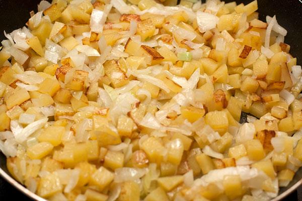 Лук нарежьте не слишком мелко и поджарьте до легкого золотистого цвета. Очищенную картошку можно натереть на крупной терке или нарезать мелкими кубиками, а затем добавить к луку.