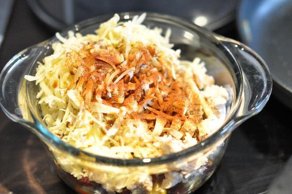 Переложите смесь со сковороды в миску и добавьте тертый сыр Чеддер. Приправьте черным перцем и вустерширским соусом или сбрызните лимоном