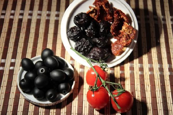 Далее самый интересный этап - в ход идут ингредиенты, обычно не допускающиеся к борщам, а именно - маслины (можно с косточками, если любите их вынимать), чернослив (желательно пожирнее), вяленые томаты (придающие всему блюду сложно определимое словами, но интересное звучание), аджика (я использую магазинную аджику по-грузински). Если на вкус маслины сами по себе сочные и нежные - можно добавить в бульон немного