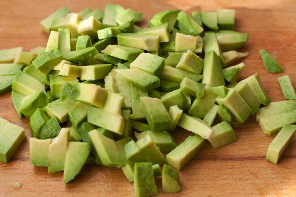 Спелый авокадо очистите, нарежьте кубиками, чуть крупнее огурца, слегка сбрызните лаймовым или лимонным соком и добавьте в салат.