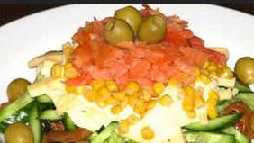 Если грибы остыли, приступайте к формированию салата. Разровняйте первый слой. Сверху на обжаренные шампиньоны положите огурцы. Нанесите немного майонезу. Потом идет слой сыра соломкой, и снова майонез. Кукурузу выкладываем на сыр. Красиво сверху, как шапочку, кладем, ломтики семги. В качестве украшения возьмите оливки и уложите по кругу блюда. Салат с жареными грибами готов, можно ставить на стол.