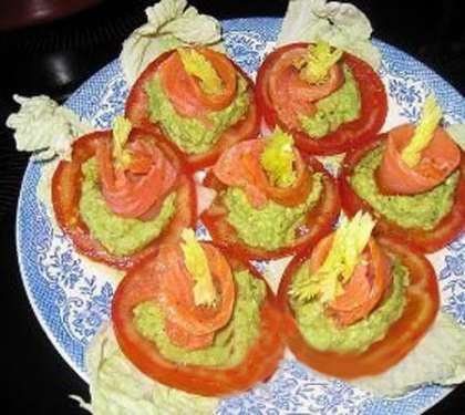 Закуска с авокадо и красной рыбойЧистим авокадо, режем на куски и взбиваем в блендере. Массу солим и перчим, добавляем лимонный сок. Плотные помидоры нарезаем кружками. На каждый кружок кладем пасту из авокадо, разравниваем в виде аккуратной горки. Семгу нарезаем кусочками и сворачиваем рулетиком. Красиво раскладываем ее поверх пасты из авокадо.