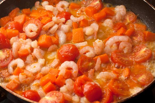 Следом добавьте очищенные креветки. Можно налить немного овощного бульона или воды, в которой варилась паста.  Тушите 3-5 минут, чтобы тыква стала абсолютно готовой, но не начала разваливаться.