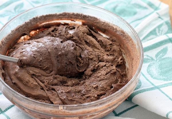 В это время доделаем крем. За три часа наша заготовка должна загустеть так, чтобы её с усилием можно было перемешивать ложкой. Добавляем в неё сахарную пудру, какао-порошок и соль и тщательно мешаем, пока не получится гладкий густой крем.