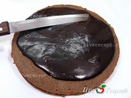 Теперь покрываем торт шоколадной глазурью. Удобнее это делать на решетке, но можно обойтись и без нее. Глазурь должна полностью покрыть всю поверхность торта и бока. Шоколадную глазурь выливаем на середину (побольше), а затем при помощи  специальной лопаточки или большого широкого ножа распределяем глазурь. Излишки глазури будут произвольно стекать, и покрывать бока торта. Ставим торт в холодильник.