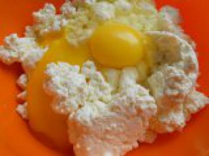 3 В творог добавить яйца. Приготовить тесто: творог выложить в глубокую миску, размять руками. Добавить яйца, посолить по вкусу. Снова руками перемешать до однородной массы.