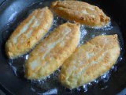 8 Обжарить пирожки. В сотейник влить растительное масло (масла должно быть достаточно, чтобы пирожки почти полностью были в масле), разогреть. Выложить подготовленные пирожки в масло и обжаривать на среднем огне с двух сторон до румяной корочки.