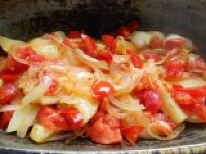 3 Выложить лук и помидоры на картофель. Выложить обжаренные лук с помидорами на картофель, разровнять ложкой. Посолить.