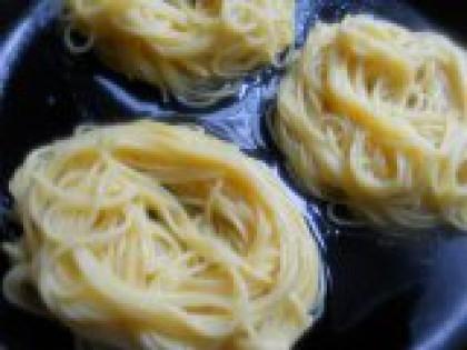 3 Выложить макароны на сковороду. Хорошо перемешать макароны с яйцом. Влить в холодную сковороду немного растительного масла и воды и выложить спагетти в виде