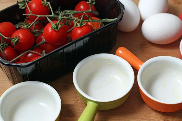 Вымойте помидоры и яйца, формочки для запекания смажьте маслом. духовку разогрейте до 200 градусов.