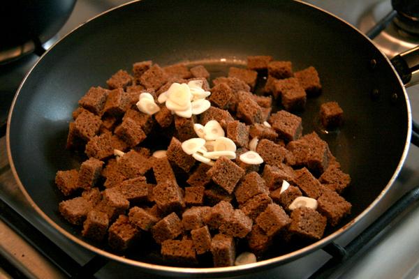 Нарезаем небольшими (1см х 1см) кубиками мякоть черного хлеба, мелко шинкуем чеснок и подсушиваем все на медленном огне в оливковом масле минут 10.