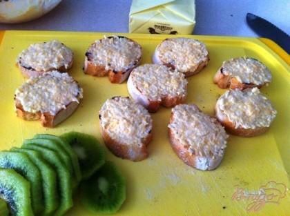Намазываем багет сырной начинкой. Чистим киви и нарезаем кружочками.