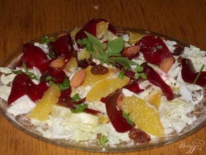 Готово! На блюдо выкладываем капусту, затем свеклу и апельсин. Поливаем салат заправкой, сверху выкладываем орехи и изюм. Украшаем салат зеленью. Приятного аппетита!