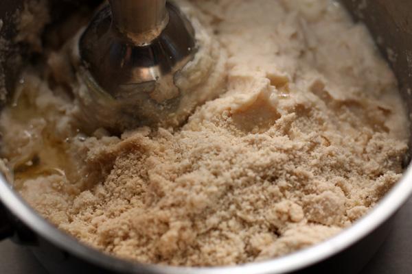 Кунжут смелите в порошок (в блендере или кофемолке) и добавьте в пюре из фасоли. Туда же подливайте оливковое масло и продолжайте измельчать, пока не получится консистенция паштета — густая, но пластичная.