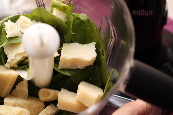 Листья шпината положите в блендер вместе с кусочками пармезана и очищенным чесноком.