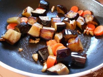 С приготовлением мы закончили. Теперь будем готовить гарнир. Отожмем баклажаны от жидкости, которую они выделили. В сковороду наливаем оливковое масло, прогреваем его и добавляем баклажаны, морковь и чеснок.