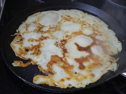 Испечь блины: на горячую сковороду налить половником тесто и раскатать по сковороде.Обжарить тесто на среднем огне примерно минуту и перевернуть. Обжарить еще минуту