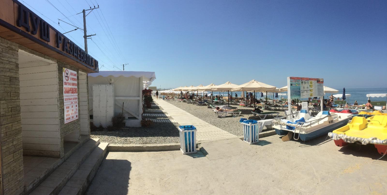На пляже - шале с лежаками и розетками, навесы, зонты, водные горки для детей, лежаки