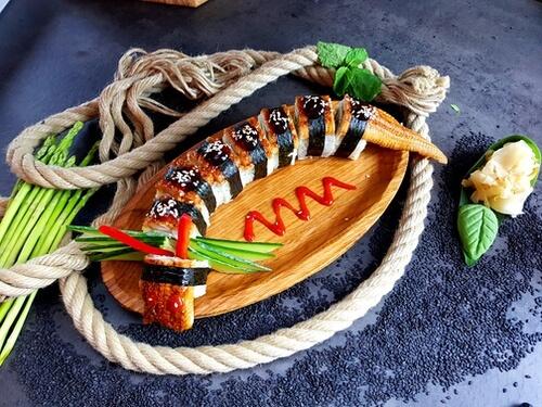ДРАКОНАроматный копченый угорь с «Унаги» соусом и кунжутом, тигровая креветка, сливочный сыр, авокадо, соус «Шрирача» и декор.