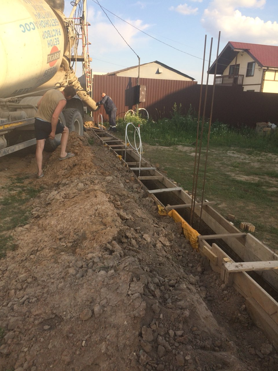 Заливка бетона в опалубкуленточного фундамента для забора