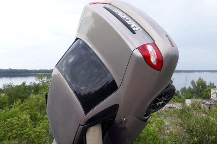 Машина вылетела в обрыв и повисла на столбе