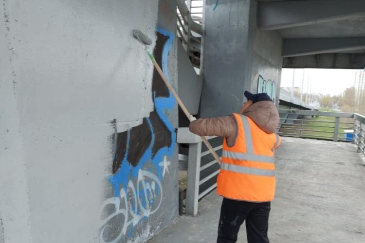 Коммунальщики в майские праздники закрашивают граффити на мосту Победы и убираются в парках